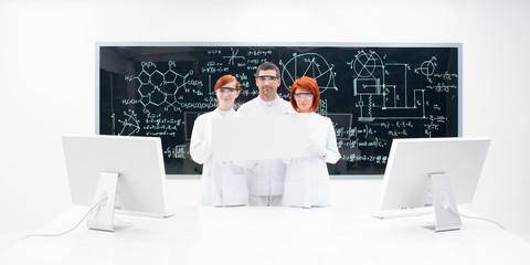 Three lab technicians dressed in white