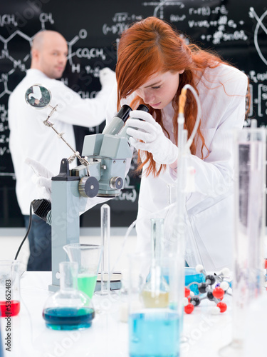 Lab technician looking down a microscope
