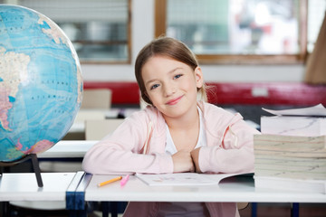 Cute Schoolgirl Smiling With Globe And Books At Desk
