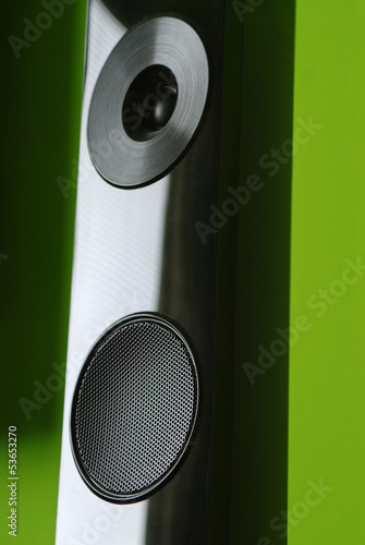 Closeup of black home cinema speaker on green background © sushaaa