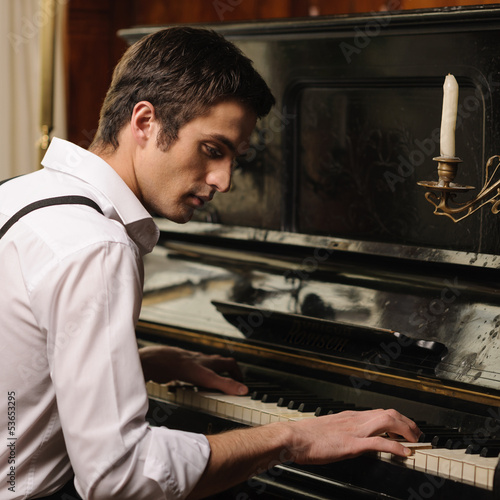 Making music. Profile of a handsome young men playing piano