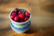 Ripe cherries in a rustic recipient on a wooden surface.
