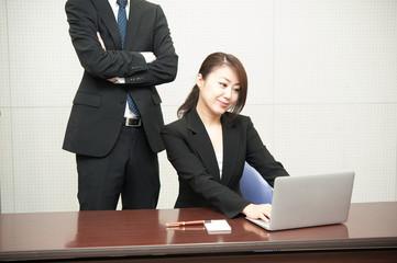 男性の上司から指導を受ける女性