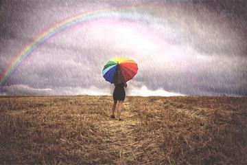 Mujer con paraguas de colores bajo la lluvia en el campo