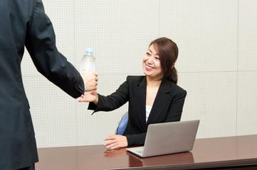 オフィスで水分補給する女性写真