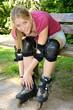 Junge sportliche Frau zieht Inliner an