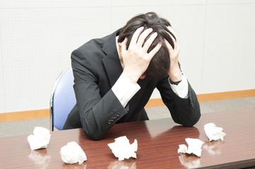 仕事に失敗して悩む男性社員