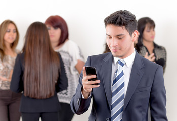 Hispanic man using a cellphone with peers