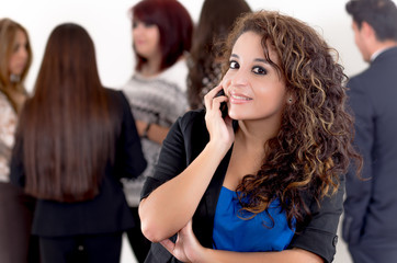 Hispanic woman using a cellphone with peers