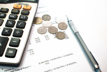coins and calculator and pen on financial figure