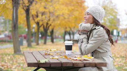 Fall woman sitting in autumn park smiling happy
