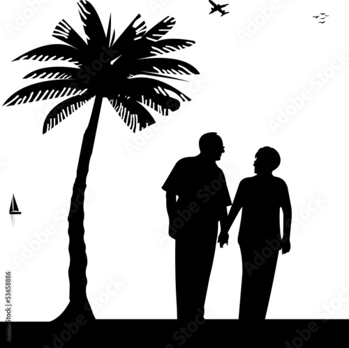Lovely retired elderly couple walking on the beach