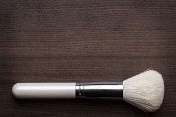 white make-up brush on wooden table