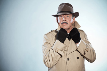 Vintage detective man with mustache and hat. Wearing raincoat. S