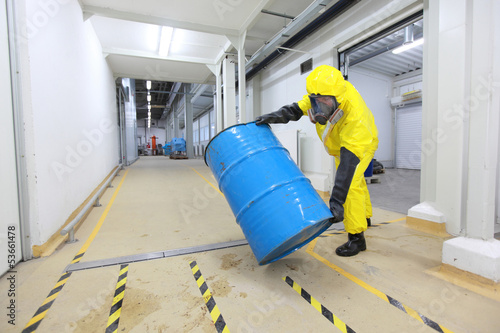 technician in uniform rolling barrel with hazardous substance