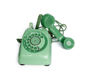 An old green vintage rotary style telephone off the hook