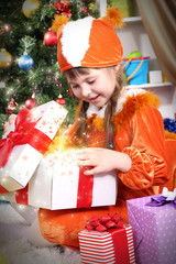 Little girl in suit of squirrels opens gift in festively