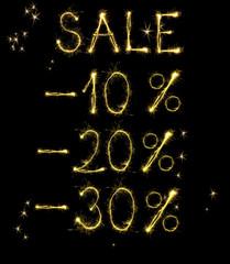 Sale percentage made of sparklers on black background