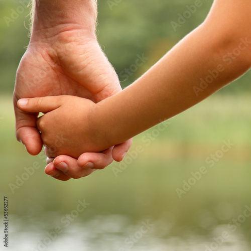 father's hand lead his child son in summer nature background