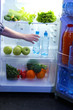 Woman's hand reaching out for food from the refrigerator, close