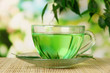 Transparent cup of green tea on bamboo mat, on nature