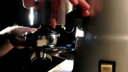 Barista takes ground coffee from grinder