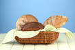 Bread in wicker basket, on wooden table, on color background