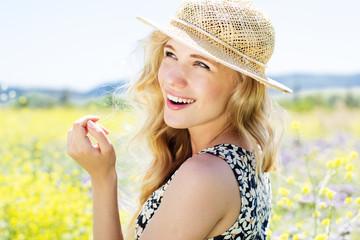 Portrait of beautiful blonde girl in the field of flowers