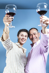 Happy couple toasting with red wine