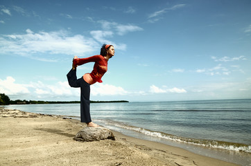 Woman practising a yoga balance by the sea