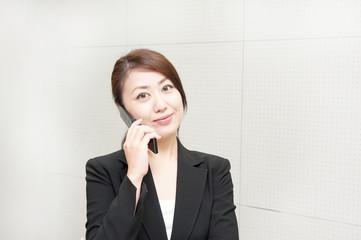 オフィスで携帯電話で電話をするスーツの女性