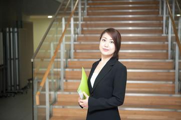 ファイルを持って階段の前に立つスーツの女性