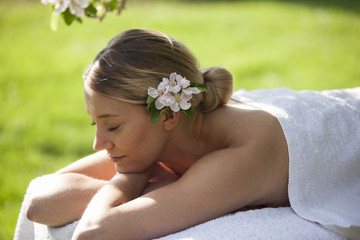 A young woman laying on a massage table, eyes closed