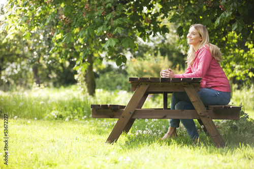 A young woman sitting at a garden bench holding  mug
