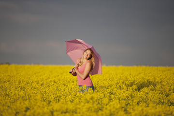 A young woman in a rape seed field holding a pink umbrella