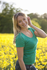 A young woman standing in a rape seed field smiling