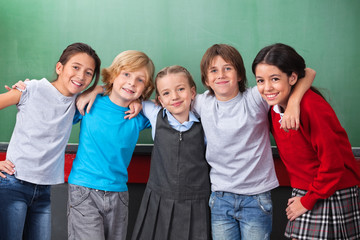 Cute Schoolchildren With Arms Around Standing Together In Classr