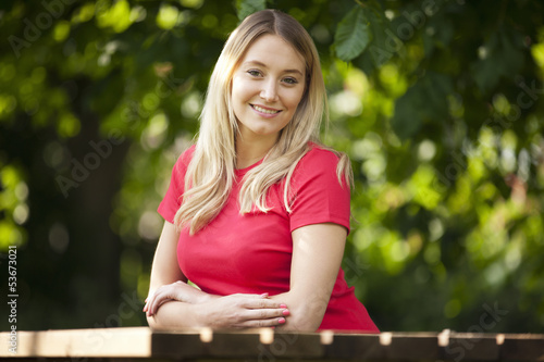 A young woman sitting at a garden bench, smiling