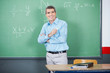 Male Teacher Standing Arms Crossed Against Board