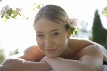 A young woman laying on a massage table under a tree in blossom
