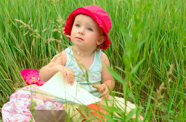cute little girl sitting in the green grass