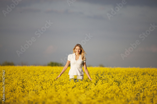 A young woman walking through a rape seed field