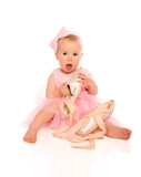 Little baby girl in a pink ballerina dress with pointe shoes