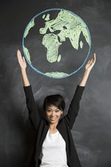 Asian woman with chalk globe drawn on blackboard.