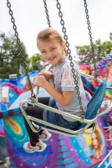Kleines Mädchen auf dem Kettenkarussell