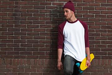 Hip cool urban fashion skateboarder with woolen hat posing in fr