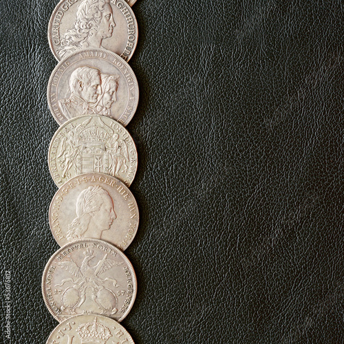 Ancient silver coins on a leather surface