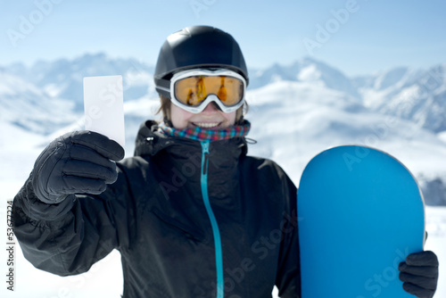 Snowboard girl with blank card smiling