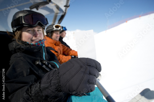 Winter sport girl in chair lift with ticket