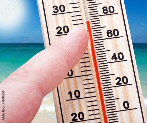 Leinwandbild Motiv Thermometer in hand shows the intense heat